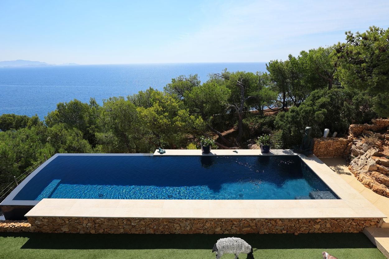 piscine à débordement avec habillage mur en pierres sur un côté